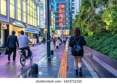 Tokyo, Japan - May 20, 2019: A young woman explores Shinjuku Kabukicho, and area known for its vibrant nightlife and neon lights.