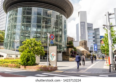 Tokyo, Japan - May 20, 2019: People wander past a  building in the Roppongi Hills  complex, a large area encompassing shopping and dining as well as museums, in the Roppongi neighborhood.