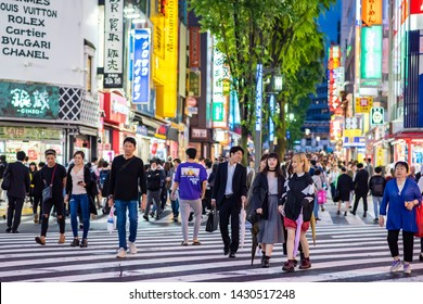 Tokyo, Japan - May 20, 2019:  People cross the street in the beautiful and famous Shinjuku neighborhood. More than three hundred thousand people live in Shinjuku.