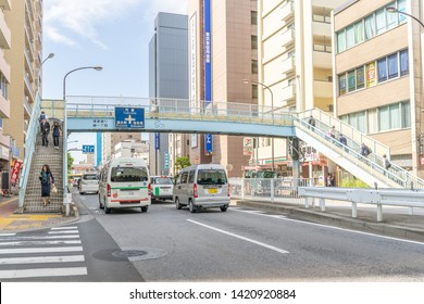 Tokyo, Japan - May 22, 2019: Cars under a pedestrian walkway in the Ryogoku Sumida City area. Tokyo has many bridge walkways as pedestrian safety measures.