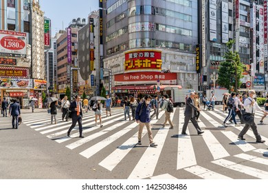 Tokyo, Japan - May 24, 2019: People cross the street at a busy intersection in Shinjuku, a busy area where more than three hundred thousand people live.