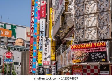 Tokyo, Japan - May 24, 2019: Japanese architecture of stacked street signs on multi-story buildings, in the beautiful Shinjuku Kabukicho neighborhood, including an okonomiyake restaurant.