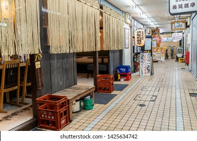 Tokyo, Japan - May 24, 2019: Indoor exterior of restaurants in the Koenji neighborhood, where many bars and restaurants are beneath railroad tracks because of high population density.
