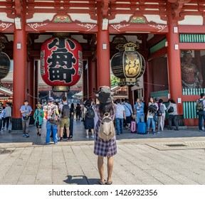 Tokyo, Japan - May 25, 2019: A tourist takes a photo of the Kaminarimon or Thunder Gate at the beautiful Senso-Ji Shrine, in Asakusa, an area known for the shrine and its historic architecture.