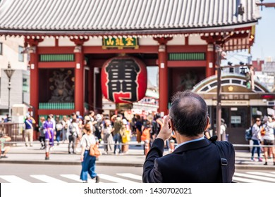 Tokyo, Japan - May 25, 2019: People gather at the gate, called Kaminarimon or Thunder Gate, at the entrance to the Senso Ji Temple in historic Asakusa.