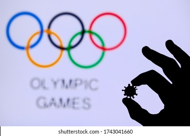 TOKYO, JAPAN - MAY 25, 2020: Hands silhouette holds covid 19 virus, Olympic circle in background