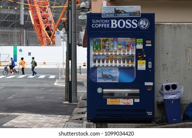 TOKYO, JAPAN - May 26, 2018: A vending machine selling cold bottled and canned drinks on a sidestreet in Sendagaya. The construction site of the Tokyo Olympic Stadium can be seen in the background.