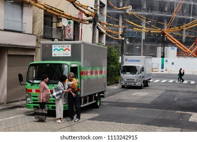 TOKYO, JAPAN - May 26, 2018:  Delivery driver giving people directions on a Tokyo street with under-construction 2020 Tokyo Olympic Stadium in the background. Above the street are electricity cables.