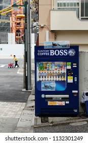 TOKYO, JAPAN - May 26, 2018: A vending machine selling cold bottled and canned drinks on a Setagaya sidestreet. The construction site of the Tokyo Olympic Stadium is in the background.