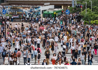 TOKYO, JAPAN - MAY 28, 2017: Pedestrians walk at Shibuya Crossing. The crossing is one of the world's most famous examples of a Scramble Crosswalk.