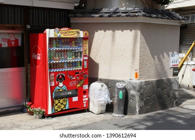 TOKYO, JAPAN - May 3, 2019: A drinks vending machine with special Coca Cola livery  with a geisha and carp in front of a public bath in Tokyo's Kagurazaka area.