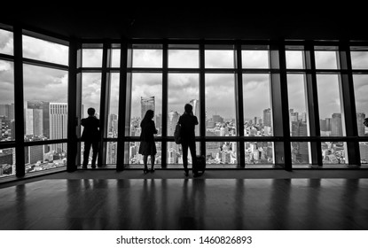 Tokyo, Japan - May 3 2019: A silhouette of business tourist observing the Tokyo business district skyline from the observation area of the Tokyo Tower.
