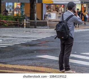 TOKYO, JAPAN - MAY 3RD, 2018. Japanese man with smartphone waiting to cross the street in Shibuya.