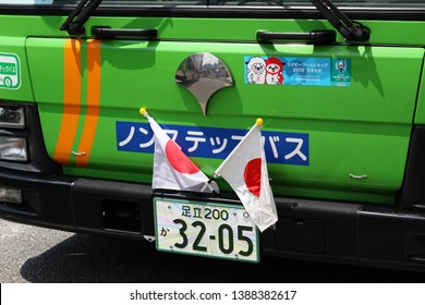 TOKYO, JAPAN - May 4, 2019: The front of a bus operating in Tokyo's Kinshicho area. National flags are on it due to a national holiday. It also has stickers with Ren and G, the 2019 Rugby World Cup.