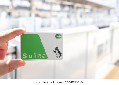 Tokyo, Japan - May 4, 2019 : Man hold Suica pass with the blurred train station background, Suica is a prepaid card for travelling with train, bus and shopping in Japan.