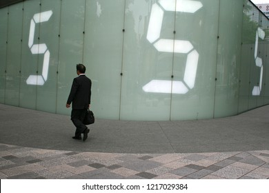 Tokyo, Japan - May 5, 2008: A salaryman walking past a digital wall in Roppongi, Tokyo.