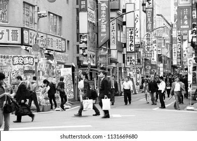 TOKYO, JAPAN - MAY 8, 2012: Commuters hurry in Shinjuku district, Tokyo. Shinjuku is one of the busiest districts of Tokyo, with many international corporate headquarters located here.