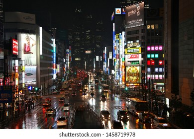 TOKYO, JAPAN - MAY 9, 2012: People drive in the rain in Shinjuku district, Tokyo. Shinjuku is one of special wards of Tokyo. 337,556 people live here.
