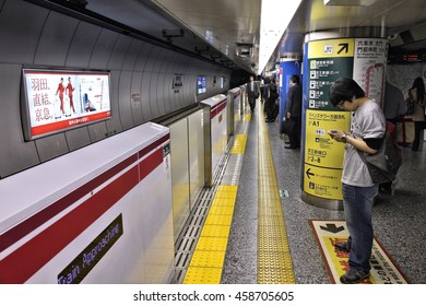 TOKYO, JAPAN - MAY 9, 2012: People wait atTokyo Metro station. With more than 3.1 billion annual passenger rides, Tokyo subway system is the busiest worldwide.