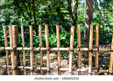 Tokyo, Japan Meiji shrine closeup of tied bamboo wooden fence with strings and green tree foliage by forest on sunny day