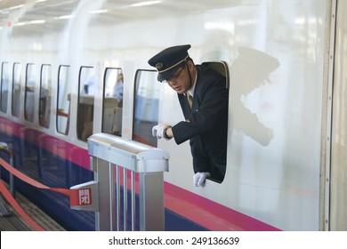 TOKYO, JAPAN - NOV 10: Shinkansen (Bullet Train) conductor checks time for prompt departure at Tokyo station, on November 10, 2014, in Tokyo, Japan. Shinkansen trains are known for being punctual.