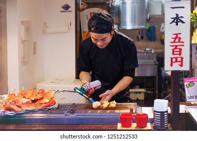 Tokyo, Japan - Nov 13, 2018: Japanese man cooks tuna fish with open fire and smile on his face at famous Tsukiji fish market, Tokyo. Hieroglyphic inscription: 1 piece 500 yen.