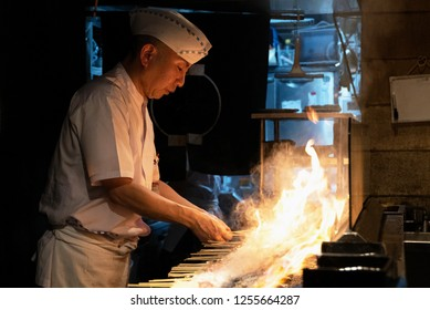 TOKYO, JAPAN - NOV 23: Cook in a yakitori restaurant in Tokyo, Japan on November 23, 2018. Yakitori is Japanese barbecue with skewers.
