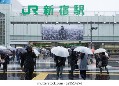 Tokyo, Japan - Nov 24, 2016: Pedestrians outside of Shinjuku Stations walking under snow fall.It is the first time in 54 years to have snow in November in Kanto area.