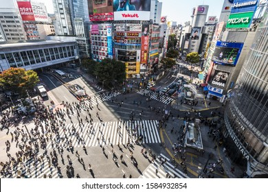 Tokyo, Japan - Nov 5, 2019: Crowded people walking, car traffic on Shibuya scramble crossing, high angle view. Tokyo tourist attraction, Japan tourism, Asia transportation or Asian city life concept