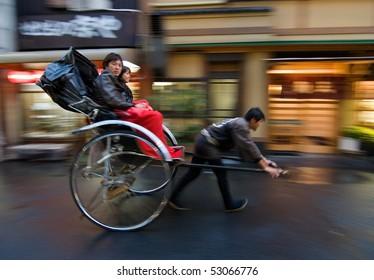 TOKYO, JAPAN - NOVEMBER 10:  Two people on a rickshaw being pulled on the street November 10, 2007 in Asakusa, Tokyo, Japan.