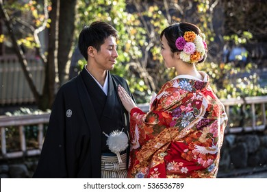 TOKYO, JAPAN - NOVEMBER 11, 2016: Japanese couple wearing traditional japanese kimonos walk on the street of Gion, Kyoto old town, Japan. Kimono is a Japanese traditional garment.