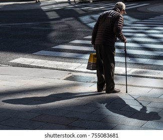 TOKYO, JAPAN -NOVEMBER 13TH 2017. Old man with a cane waiting to cross the road in Ginza.