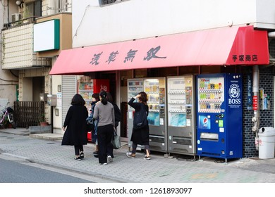TOKYO, JAPAN - November 17, 2018: People walk past a row vending machines in front of a liquor store in Tokyo's Kappabashi area. One machine contains cigarettes, two beer, and the other soft drinks.