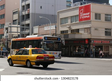 TOKYO, JAPAN - November 17, 2018: View of a street in Taito Ward in Tokyo's Asakusa area with a taxi and a local bus. A branch of Mister Donut is in the backgroud. Some motion blur.