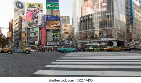 TOKYO, JAPAN - NOVEMBER 18, 2016. Taxis driving at Shibuya Crossing in Tokyo. Shibuya crossing is one of busiest places in Tokyo and one of the most popular meeting points in the city.
