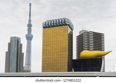 TOKYO, JAPAN - November 19, 2018:  The Asahi Flame and Beer Tower with Tokyo Skytree near Sumida River in Tokyo, Japan.