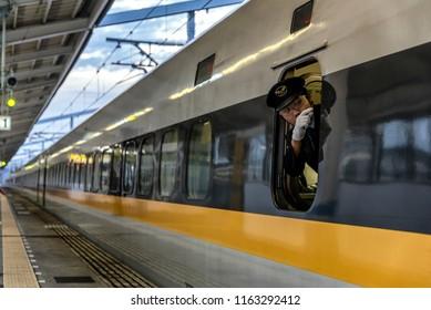 TOKYO, JAPAN - NOVEMBER 20, 2015: Shinkansen Cabin attendant signs for officer train departure on the railway station in Tokyo, Japan.