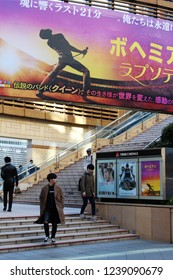 TOKYO, JAPAN - November 23, 2018: Visitors walk past and under movies Roppongi Hills Toho movie theater posters, including a large one for Bohemian Rhapsody, in Tokyo's Minato Ward.