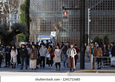 TOKYO, JAPAN - November 23: People waiting to use the Sukiyabashi scramble crossing in front of Ginza's Sony Park with the Renzo Piano-designed Hermes building in the background.