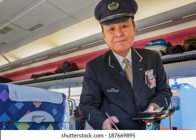 TOKYO, JAPAN - NOVEMBER 23: Train Conductor in Tokyo, Japan on November 23, 2013. Unidentified Japanese train conductor of JR train who checks for ticket and makes fare adjustment for passenger