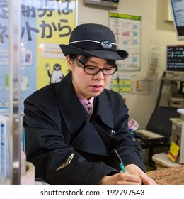 TOKYO, JAPAN - NOVEMBER 24:  Train Conductor in Tokyo, Japan on November 24, 2013. Unidentified train conductor informs people about train routes and train schedules