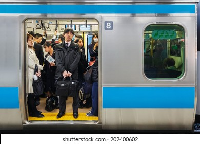 TOKYO, JAPAN - NOVEMBER 26: Train Commuters in Tokyo, Japan on November 26, 2013. Tokyo train is always packed with people all through the day and especially in rush hours