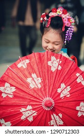 TOKYO, JAPAN - NOVEMBER 28, 2018: Japanese girl with umbrella posing during Shichi-Go-San day at Shinto shrine. Shichi-Go-Sun is annual festival day in Japan for 3, 5 and 7 years old children.