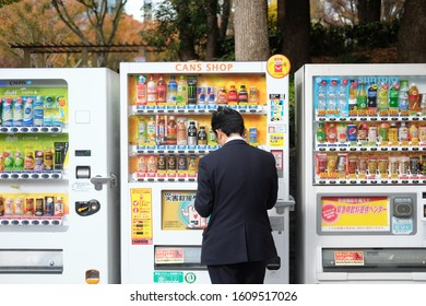 Tokyo / Japan - November 28th 2017: Salaryman buying on vending machine. Japanese man worker buys drinks on colourful vending machine in Tokyo, Japan