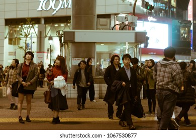 TOKYO, JAPAN - NOVEMBER 30, 2017: Two Japanese girls in vintage clothes waiting for their friend on a crowded street by the famous and busy Shibuya Crossing.