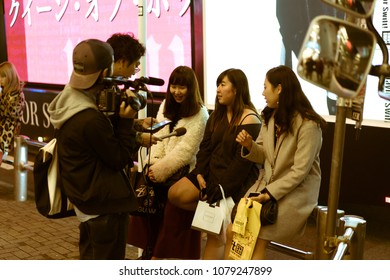 TOKYO, JAPAN - NOVEMBER 30, 2017: Three young Japanese girls being interviewed for television by two young men. The interview took place on a street close to the famous Shibuya Crossing.