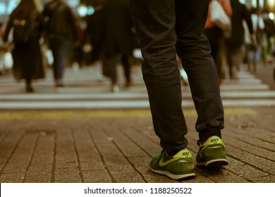 TOKYO, JAPAN - NOVEMBER 30, 2017: Close-up of male legs in jeans and green Nike sneakers waiting to cross the famous Shibuya Crossing, which is rumoured to be the busiest intersection in the world.