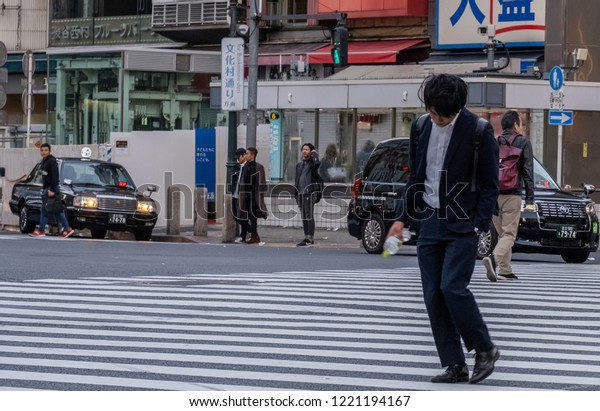 TOKYO, JAPAN - NOVEMBER 3RD, 2018. Drunk young man walking at the Shibuya pedestrian crossing in the early morning hours.