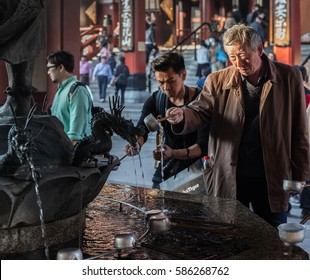 Tokyo, Japan - November 6, 2015. Fountain with dragon's statues. People cleaning hands and drinking water in purification before entering Sensoji Temple located in Asakusa.