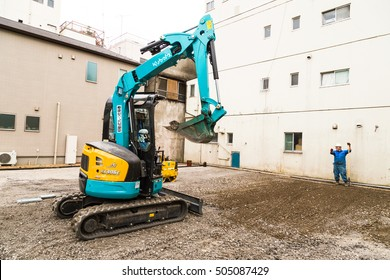 Tokyo, Japan - Obtober 26, 2016 : excavator and laborers are working on area adjustment in small construction site, Tokyo, Japan,